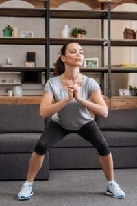 woman doing Sumo squats in her lounge room
