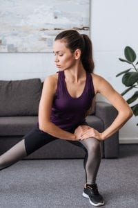 Woman doing Side Lunges in her loungeroom