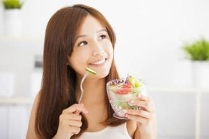 Pretty young Asian woman eating a salad