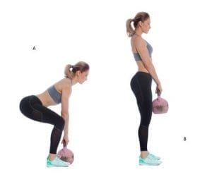 Young woman squatting with kettlebel