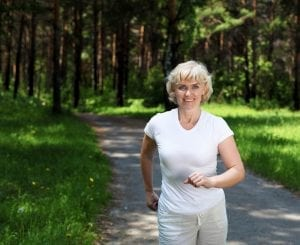 Senior woman walking for exercise in a field