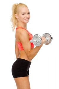 Blonde sporty woman smiling while exercising with dumbbell