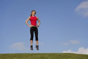 Woman doing jumping exercise outdoors
