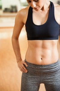Young fit woman in workout gear with a fit ab