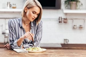 Young blonde women sitting and eating a salad