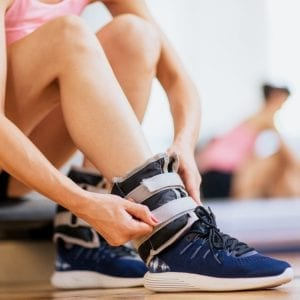 Ankle weights for women - woman strapping on ankle weights