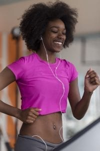Smiling African American woman jogging on treadmill