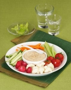 Mix of vegetables radish, carrot, cucumber, celery, cauliflower, tomatoes with sauce on a white plate