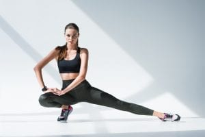 Pretty brunette woman doing stretching exercise