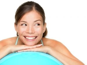 Smiling Eurasian woman leaning on fitness ball