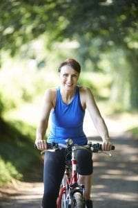 Smiling, pretty middle-aged woman cycling in the forest