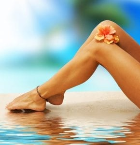 women's legs reclined in water at resort