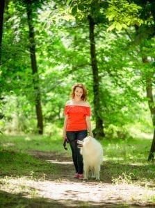 Woman walking a dog in the forest