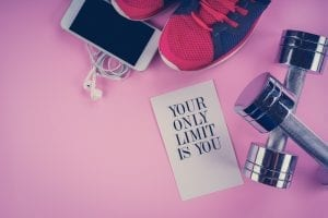 sneakers, phone and dumbbells on a pink background