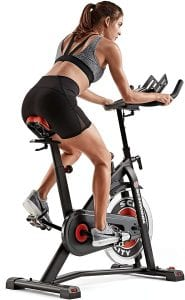 Back view of a young woman on a stationary bicycle