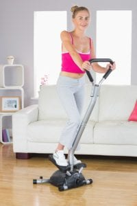 Young woman using a mini step machine at home