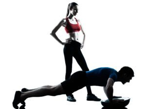 Man doing Incline Push-Ups watched by ffemale itness trainer