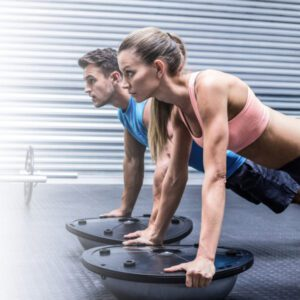Woman and man doing Plank Exercise on a balance board